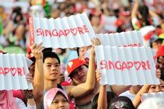 Spectateurs ondulant des bannières de Singapour pendant la répétition 2013 du défilé de jour national (NDP) Image libre de droits