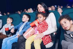 Spectateurs s'asseyant dans le théâtre de film et appréciant le film, mangeant des casse-croûte photo stock