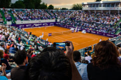 Spectator filming the QF of Bucharest Open WTA. July the 11th, 2014, tennis match between Simona Halep and Lara Arruabarrena Royalty Free Stock Image