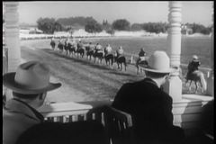 Spectators in booth watching the start of horse race stock video footage