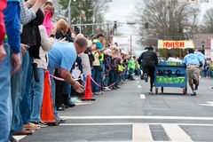 Spectators Cheer Team Pushing Bed Toward Finish Of Fundraiser Race Stock Image