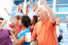 Spectators Cheering At Outdoor Sports Event. Smiling Stock Images