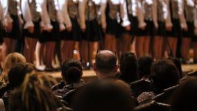 Spectators in concert hall - bald man watching choir of children singers. Telephoto stock footage