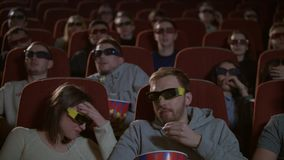 Spectators in 3D glasses strained watching scary flm. Audience in 3d cinema