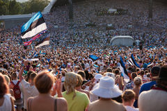 Spectators and Estonian flags at the Song Festival. Spectators are waving Estonian flags during the Song Festival in Tallinn, the capital of Estonia. The is Stock Photo