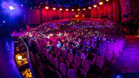 Spectators gather in the auditorium and watch the show in theatre timelapse. Large hall with red armchairs seats