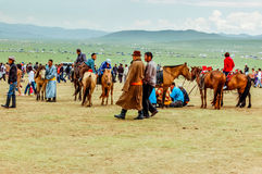 Spectators with horses, Nadaam horse race, Mongolia. Khui Doloon Khudag, Mongolia - July 12, 2010:  Spectators with horses at Nadaam horse race (some wearing Royalty Free Stock Image