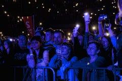 Spectators illuminated light colored spotlights, watching the pe Stock Photos