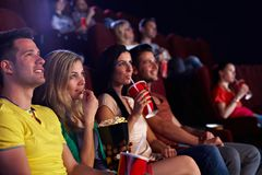 Spectators in multiplex movie theater. Young people sitting in multiplex movie theater, watching movie, eating popcorn Stock Images