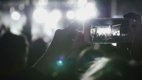 Spectators at the music concert shooting video on the smartphone royalty free stock photo