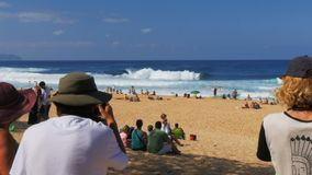 Spectators and photographers watch the wave riders at pipeline