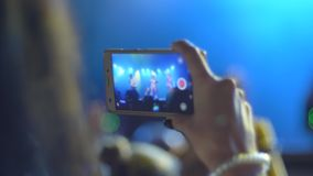 Spectators record video on mobile phone at night concert close-up on unfocused background