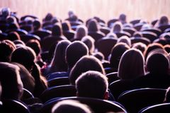 Spectators in the theater or in the cinema. Children and adults. Full house Stock Photo