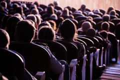 Spectators in the theater or in the cinema. Children and adults. Full house.  royalty free stock photo