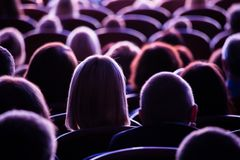 Spectators in the theater or in the cinema. Children and adults. Full house Royalty Free Stock Photo