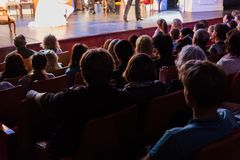 Spectators at a theater performance, in a cinema or at a concert. Shooting from behind. The audience in the hall. Silhouettes of people royalty free stock photography