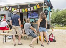 Spectators - Tour de France 2015. Quievy,France - July 07, 2015: Unidentified spectators watching on a TV the live transmission, near their caravan, during the Royalty Free Stock Images