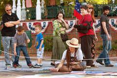 Spectators Watch Artist Draw Chalk Art On City Street Stock Photos