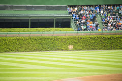 Spectators Watching Baseball from the Outfield Seating. Spectators sit in the outfield seating area of a baseball stadium Royalty Free Stock Photo