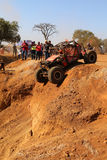 Spectators watching red car descending very steep drop into dugo. Rustenburg, South Africa - JUNE 17, 2017: National Extreme Modified 4x4 Vehicle Championship Stock Images