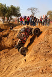 Spectators watching red car descending very steep drop into dugo. Rustenburg, South Africa - JUNE 17, 2017: National Extreme Modified 4x4 Vehicle Championship Stock Photos