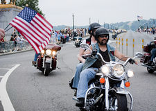 Spectators Wave US Flags During Rolling Thunder. A spectator waves American flags as motorcycles drive across Memorial Bridge from Virginia into Washington, DC Royalty Free Stock Photo