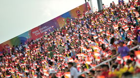 Spectators waving Singapore flags during National Day Parade (NDP) Rehearsal 2013 Stock Photos