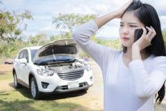 Spection delle donne ha aperto l'automobile rotta del cappuccio, utilizza lo smartphone per contattare per aiuto fotografie stock libere da diritti
