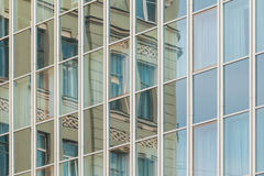 Specular facade with reflection of old building. Specular facade of office building with reflection of an old building facade Stock Photos