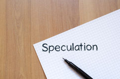 Speculation write on notebook. Speculation text concept write on notebook with pen Royalty Free Stock Image