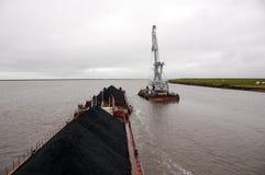 Spedisca con carbone e la gru al fiume di Kolyma Fotografie Stock Libere da Diritti