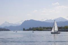Spedisca davanti ai picchi di montagne innevati delle alpi sul lago Lucerna, Svizzera centrale Le vele della barca lungo il lago Immagine Stock