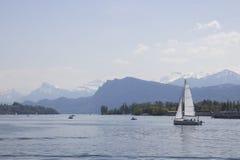 Spedisca davanti ai picchi di montagne innevati delle alpi sul lago Lucerna, Svizzera centrale Le vele della barca lungo il lago Fotografia Stock Libera da Diritti