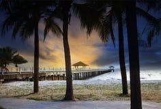 Spedisca i pilastri del porto sulla spiaggia del mare contro il bei cielo e coc oscuri fotografie stock libere da diritti