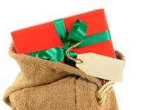 Spedisca il sacchetto o il sacco di Santa con il piccolo Natale rosso regalo ed etichetta isolati su fondo bianco Fotografia Stock Libera da Diritti