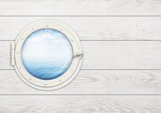 Spedisca la finestra o l'oblò sulla parete di legno bianca con Immagine Stock