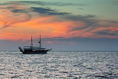 Spedisca la navigazione contro il cielo variopinto dopo il tramonto sopra il mare Fotografie Stock Libere da Diritti