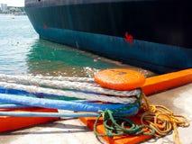 Spedisca le legame-linee assicurate in porto con rifiuti che galleggiano vicino Immagini Stock