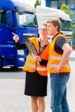Spedizioniere davanti ai camion su un deposito Fotografia Stock
