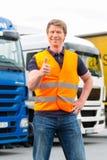Spedizioniere o driver davanti ai camion in deposito Fotografia Stock Libera da Diritti