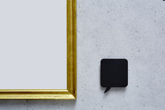 Speech bubble and empty golden frame on concrete wall Royalty Free Stock Image