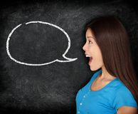 Speech bubble woman student blackboard. Woman talking in profile with black chalkboard texture as background. Funny image of mixed race female college student Royalty Free Stock Photo
