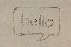 Speech bubble with the word hello written in the sand. Royalty Free Stock Photography