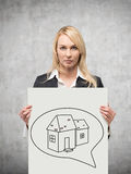 Speech bubbles with house. Businesswoman holding poster with drawing house in speech bubbles Royalty Free Stock Photos