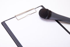 Speech or interview concept - microphone and clipboard with blan Royalty Free Stock Photos