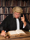 Speech of a judge. Judge with wig and gavel holding a speech to the convicted criminal royalty free stock image