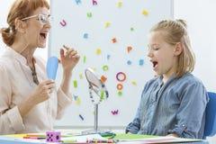 Speech and language rehabilitation. School counselor during speech and language rehabilitation with small girl Royalty Free Stock Image