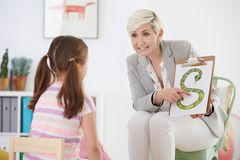 Speech pathologist with young girl. Learning the alphabet Stock Photos