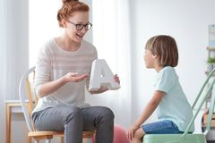 Speech therapist during private lesson. Positive female speech therapist working on articulation with a little boy during private lesson at home Stock Images