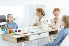 Speech therapist showing an image. Of S-shaped snake to girl in jean shirt with speech defect Royalty Free Stock Images
